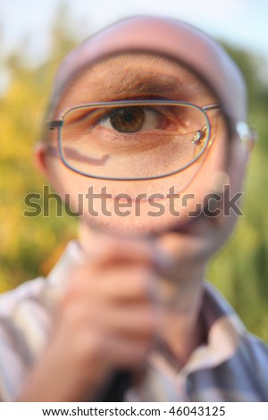 man with glasses in early fall park looking through magnifier - stock photo