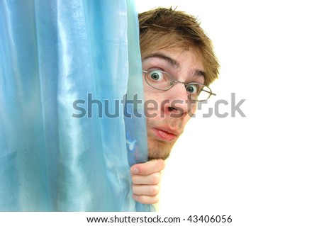 Man with glasses peeks behind a curtain with wide eyes. There is pure white copyspace to the right of him. - stock photo