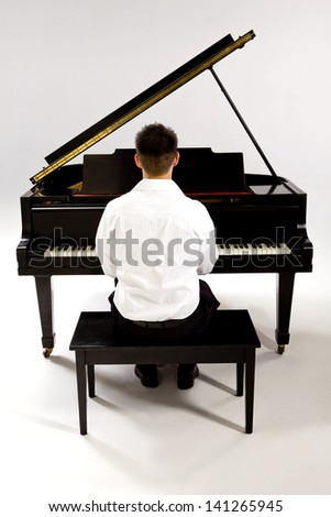Man with Grand piano wearing white shirt and black pants sitting at piano bench.