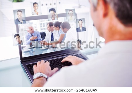 Man with grey hair typing on laptop against group of business people brainstorming together - stock photo