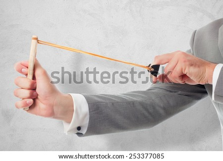 Man with grey suit closeup with slingshot. Over concrete texture - stock photo