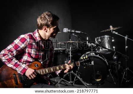 Man with guitar during concert - stock photo