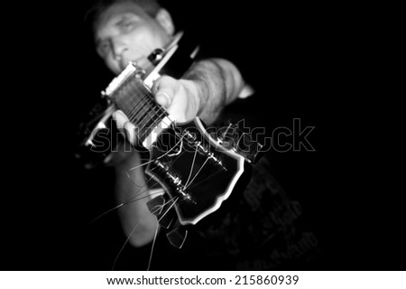 Man with guitar in a black T- shirt at the age of forty-six years old directs the guitar fretboard at the camera on a black background - stock photo