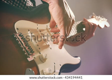 Man with guitar on color background - stock photo