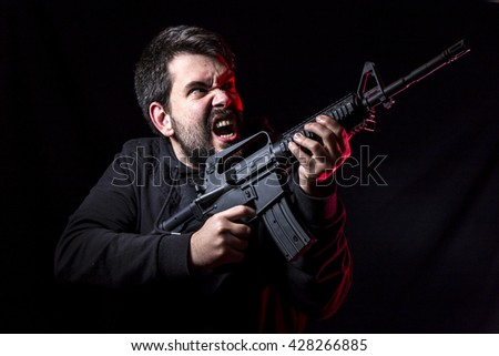 man with gun against grey background - stock photo