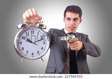 Man with gun and clock on white - stock photo