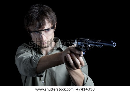 Man with gun at shooting range - stock photo