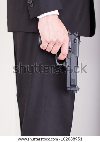 Man with gun, business suit, focus on the gun - stock photo