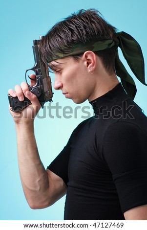 Man with gun close up on a blue background. - stock photo