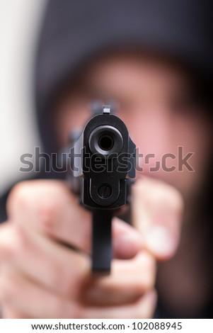 Man with gun, gangster, focus on the gun - stock photo