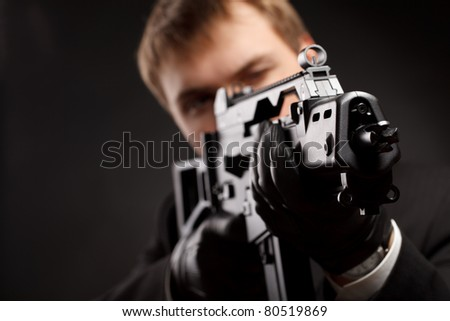 Man with gun over gradient gray - stock photo