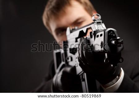 Man with gun over gradient gray - stock photo