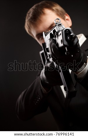 Man with gun over gradient gray. Focused on aim. - stock photo