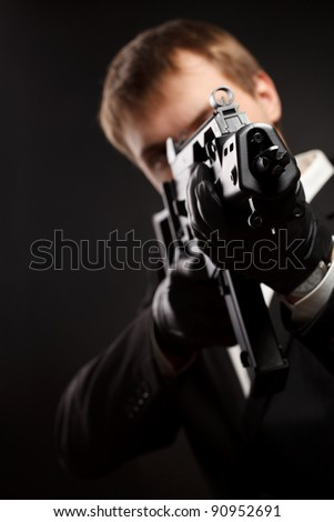 Man with gun over gradient gray. Focused on gun. - stock photo