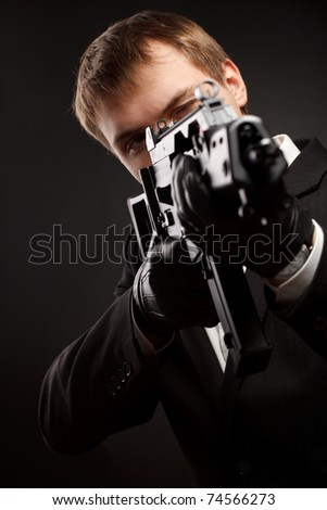 Man with gun over gradient gray. Focused on head - stock photo