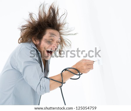 Man with hair standing on end plugging bared wire into a wall socket - stock photo