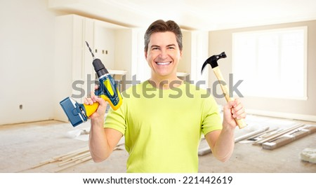 Man with hammer and drill. House renovation and construction. - stock photo