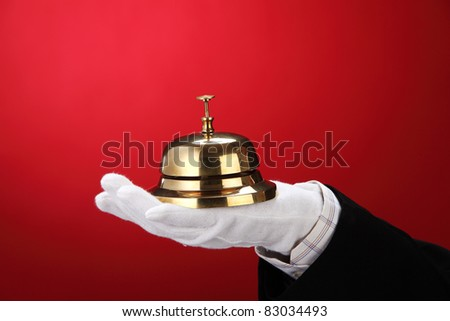 man with hand glove holding a sercive bell - stock photo