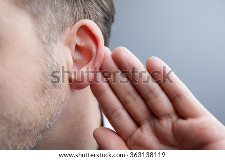 Man with hand on ear listening for quiet sound or paying attention - stock photo