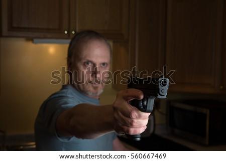 Man With Handgun In Dark Kitchen, Gun In Focus Only, Trigger Finger In The