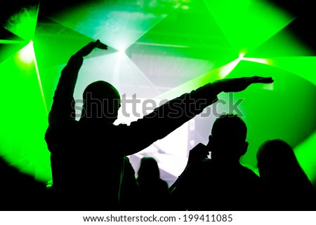 Man with hands in the air at nightclub party rave - stock photo