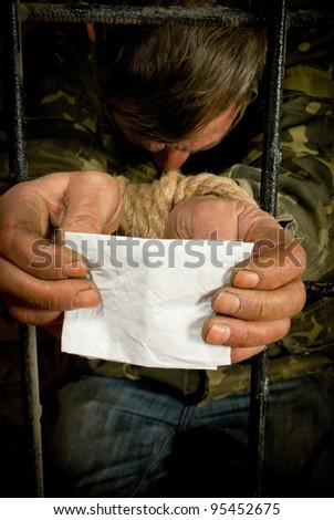Man with hands tied up with rope behind the bars - stock photo