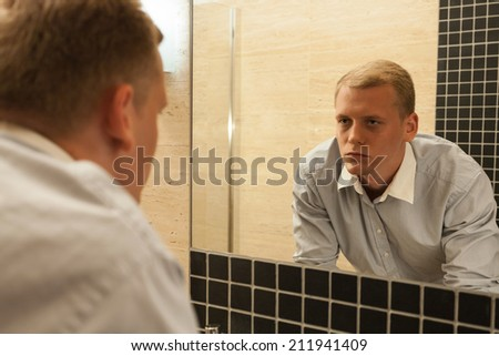 Man with hangover in a bathroom, horizontal - stock photo