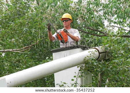Man with hard hat and chainsaw getting ready to trim a tall tree branch. - stock photo