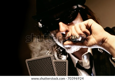 Man with hat and cigar playing underground poker. - stock photo
