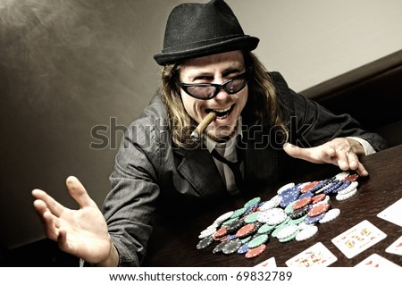 Man with hat and glasses playing underground poker.