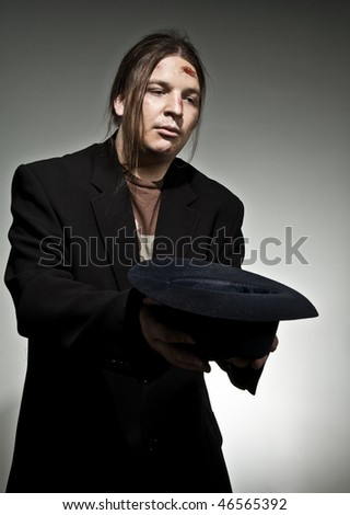Man with hat begging for some money - stock photo