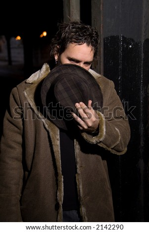 Man with hat covering his face in dark alley - stock photo