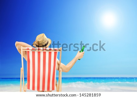 Man with hat sitting on a beach chair and holding a beer bottle, on a beach next to a sea - stock photo