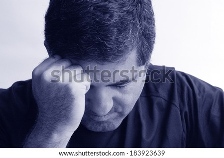 Man with headache holding his hand against the head isloated against white background with copy space. Real people concept photo of man stress, headache , depression, depressed, unhappy. (BW)
