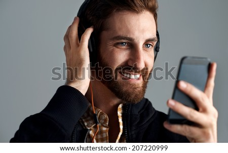 Man with headphones streaming music online with phone enjoying song with beard - stock photo