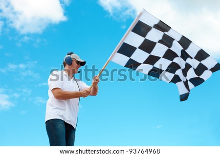 Man with headset holding and waving a checkered flag on a raceway - stock photo