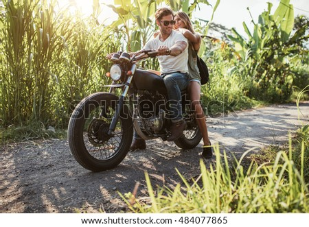 Man with her girlfriend on motorcycle. Young couple straddling motorbike on country road.