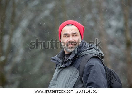 Man with hiking equipment walking in mountain forest with fallen snow  - stock photo