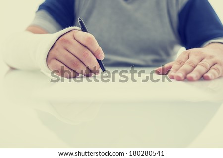 Man with his arm in a plaster cast from a fractured wrist or arm writing a letter or signing a document using his injured hand on a white table with copyspace. With retro filter effect. - stock photo