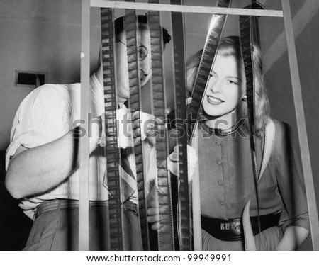 Man with his assistant looking at film reels - stock photo