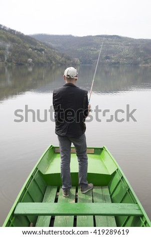 Man With His Back Towards Camera Fishing From The Boat Reeling String And Waiting Fish To Take A Bait, Forest Trees And Houses On The Hill In The Background - stock photo