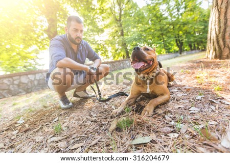 Man with his dog at park. He is looking at his dog standing with open mouth. The main subject is the dog, the man is blurred on the background. - stock photo