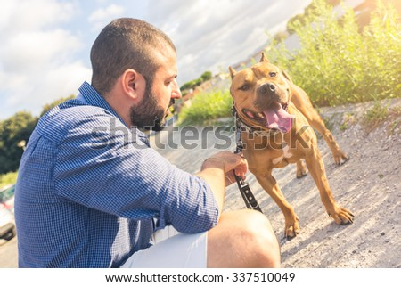 Man with his dog at park. He is looking at his dog standing with open mouth. The main subject is the dog. Concept of friendship between dogs and humans. - stock photo