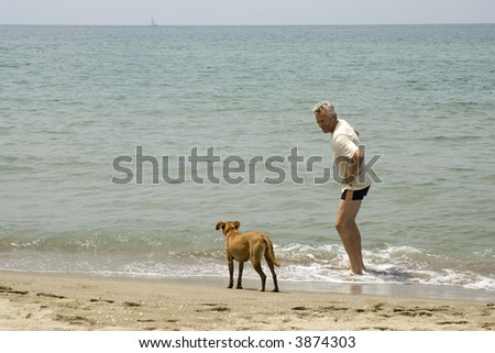 man with his dog at the beach to swim
