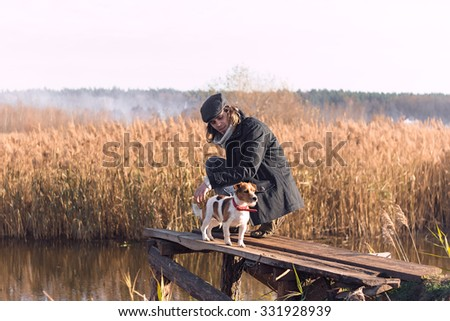 Man with his dog on the old wooden pier near by the river in sunset time. Autumn season - stock photo