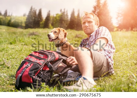 Man with his dog rest on the mountain hill  - stock photo