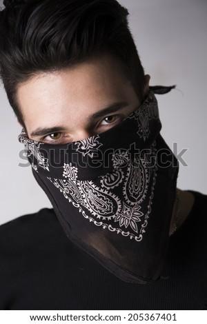 Man with his face hidden behind a bandanna stares balefully at the camera - stock photo