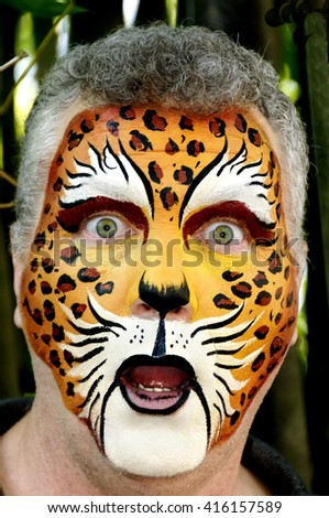 Man with his face painted like a leopard looking surprised.