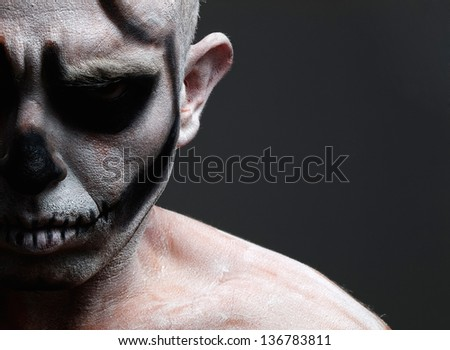 Man with his face painted with a skull and isolated on black background. Halloween background. - stock photo
