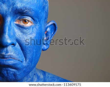 Man with his face painted with color blue. The man is sad and photographic composition leaves only half of the face and he has a sadness expression - stock photo